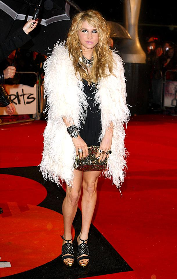"""Ke$ha looked like a rock star on the red carpet thanks to her dramatic eye makeup, tousled tresses, and funky feathered wrap. Mike Marsland/<a href=""""http://www.wireimage.com"""" target=""""new"""">WireImage.com</a> - February 16, 2010"""