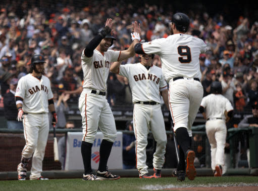 San Francisco Giants left fielder Brandon Belt (9) is welcome back to the dugout by his teammates after hitting a three-run home run against the Colorado Rockies during the seventh inning of a Major League Baseball game, Sunday, May 20, 2018, in San Francisco. (AP Photo/D. Ross Cameron)