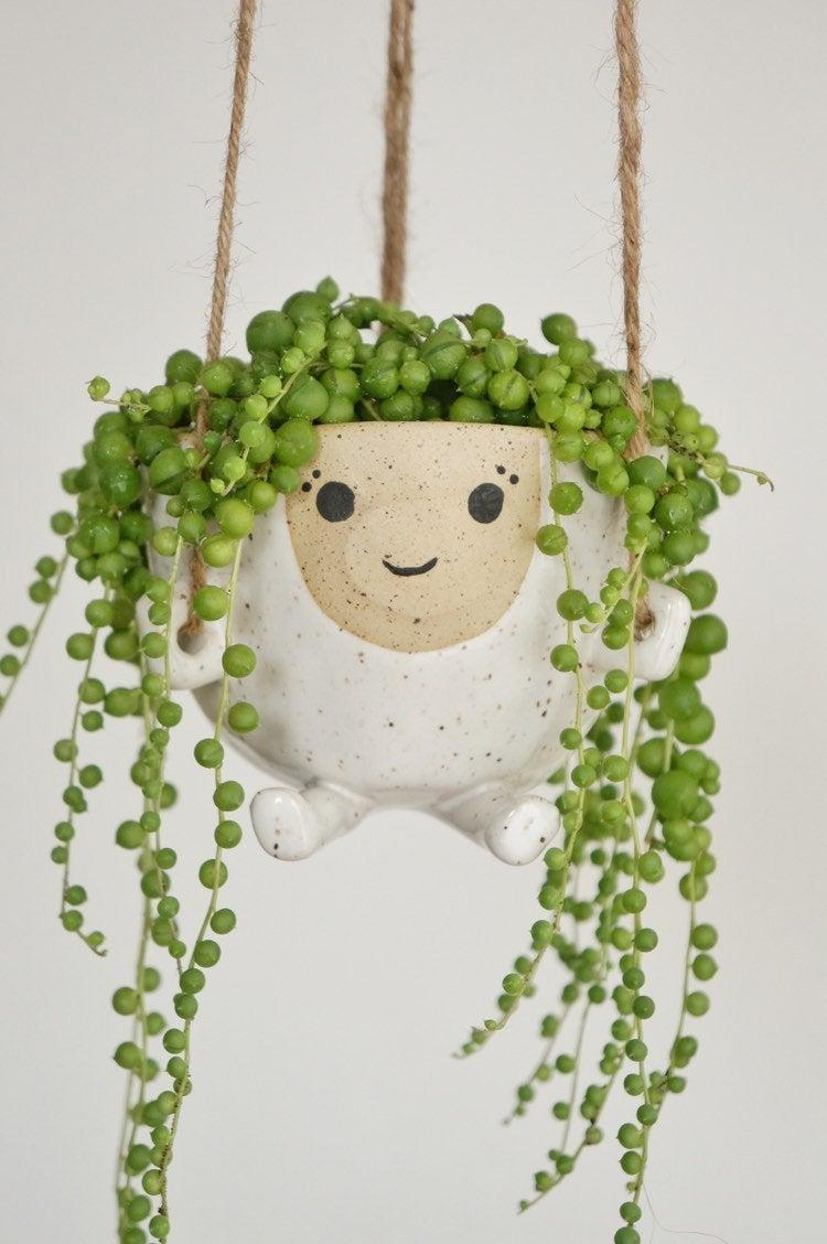"""<h2>Etsy Hanging Ema Planter</h2> <br>Showcase your greenery in the cutest way possible — aka with this playfully-shaped, speckled-stoneware planter friend. Her name is Ema. <br><br><strong>CeramicSense</strong> Hanging Planter Ema, $, available at <a href=""""https://www.etsy.com/listing/733754390/hanging-planter-ema"""" rel=""""nofollow noopener"""" target=""""_blank"""" data-ylk=""""slk:Etsy"""" class=""""link rapid-noclick-resp"""">Etsy</a><br>"""
