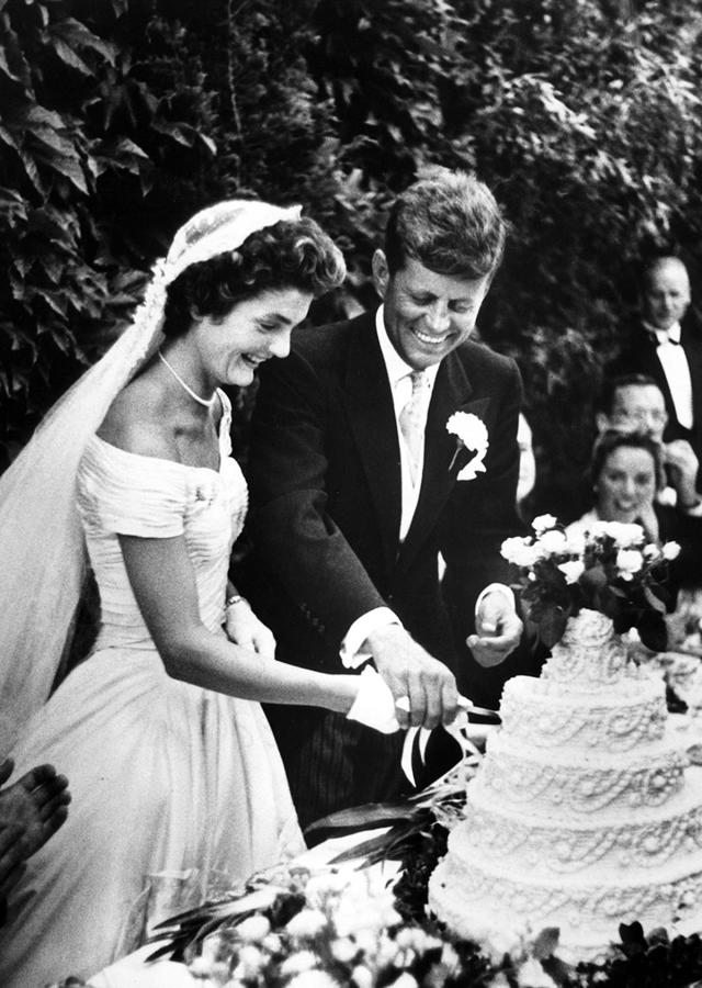 <p>Jacqueline Bouvier Kennedy and John F. Kennedy cut their wedding cake during their wedding reception at Hammersmith Farm in Newport, R.I., September 1953. (Photo: Toni Frissell Collection/Library of Congress) </p>