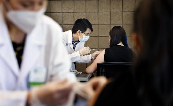 CARSON-CA-SEPTEMBER 16, 2021: Sarith Mey, center left, a pharmacist graduated intern with Rite Aid, administers a shot to CSUDH student Fritzi Bui, 29, during the final of two pop-up COVID-19 vaccination clinics hosted by Cal State Dominguez Hills and Rite Aid for CSUDH students, faculty, staff and community members on campus in Carson on Thursday, September 16, 2021. (Christina House / Los Angeles Times)