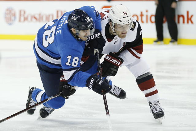 Winnipeg Jets' Bryan Little (18) and Arizona Coyotes' Christian Fischer (36) fight for position during second-period NHL hockey game action in Winnipeg, Manitoba, Saturday, Oct. 20, 2018. (John Woods/The Canadian Press via AP)