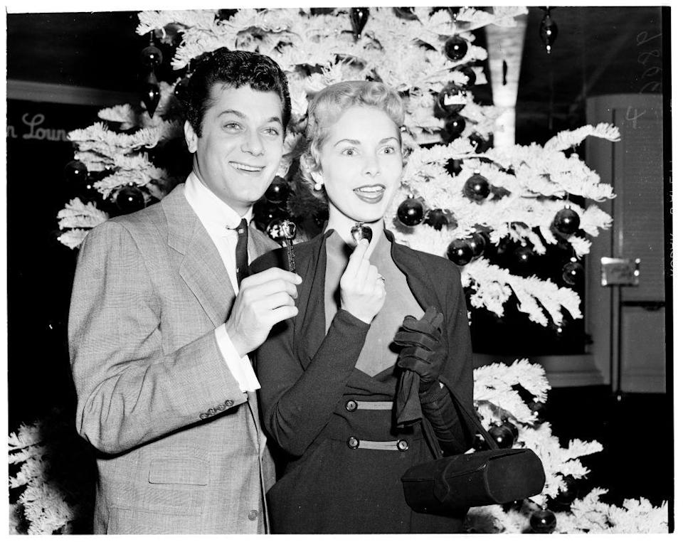 <p>Tony Curtis wore a grey sport coat at an event at the Beverly Hills Hotel in Los Angeles with his wife, Janet Leigh. Sure, the look isn't in-your-face festive, but they did pose in front of the tree.</p>