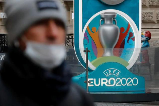 FILE PHOTO: A person wearing a protective face mask walks past the Euro 2020 countdown clock in Saint Petersburg