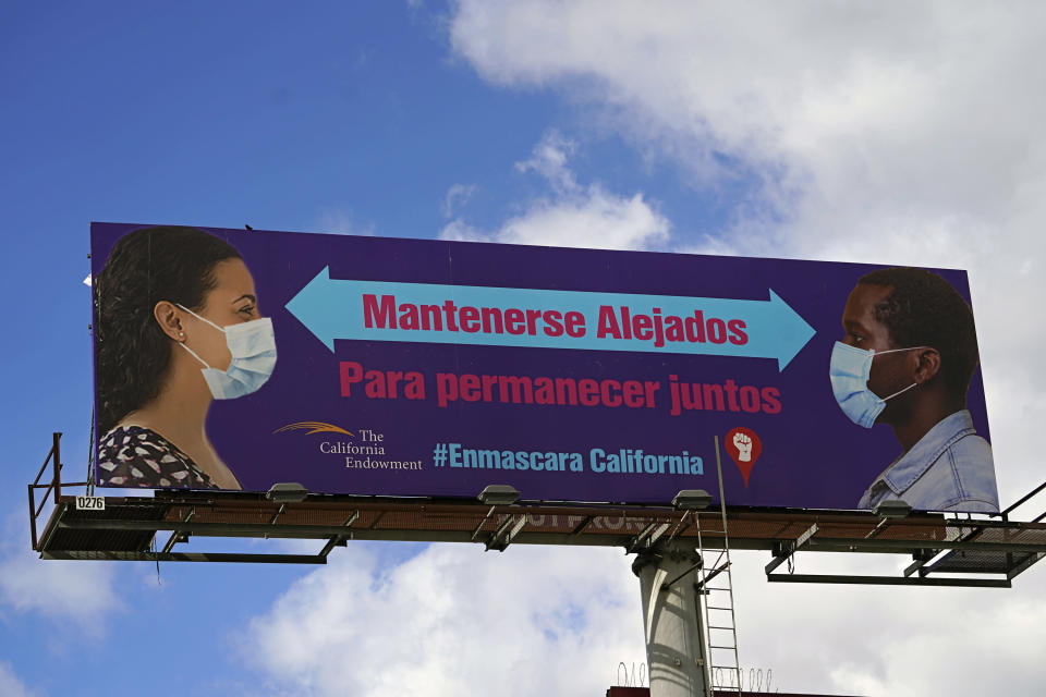 "A giant banner reads in Spanish, ""Stay Apart to Stay Together,"" in Los Angeles Monday, Jan. 25, 2021. California has lifted regional stay-at-home orders statewide in response to improving coronavirus conditions. Public health officials said Monday that the state will return to a system of county-by-county restrictions intended to stem the spread of the virus. Local officials could choose to continue stricter rules. The state is also lifting a 10 p.m. to 5 a.m. curfew. (AP Photo/Damian Dovarganes)"