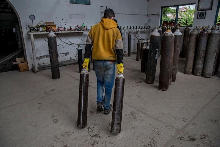 """A worker moves empty oxygen cylinders for refilling at a gas supplier facility in Srinagar on May 11, 2021.<span class=""""copyright"""">Dar Yasin—AP</span>"""