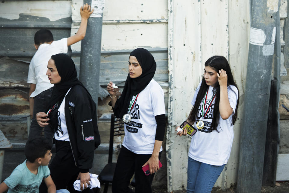 FILE - In this Friday, June 4, 2021 file photo, Palestinian activist Muna el-Kurd, center, wears a medal from a marathon as she leaves the site where Israeli police fired tear gas during clashes in the Silwan neighborhood of east Jerusalem. On Sunday, Israel arrested el-Kurd, a Palestinian protest leader in the contested Sheikh Jarrah neighborhood of Jerusalem, a day after forcefully detaining a prominent journalist there. (AP Photo/Maya Alleruzzo, File)