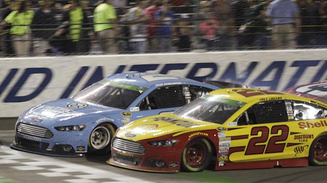 Joey Logano (22) and Brad Keselowski (2) approach the start-finish line in the closing laps of the NASCAR Sprint Cup Auto race at Richmond International Raceway in Richmond, VA., Saturday, April 26, 2014. Logano won the race. (AP Photo/Steve Helber)