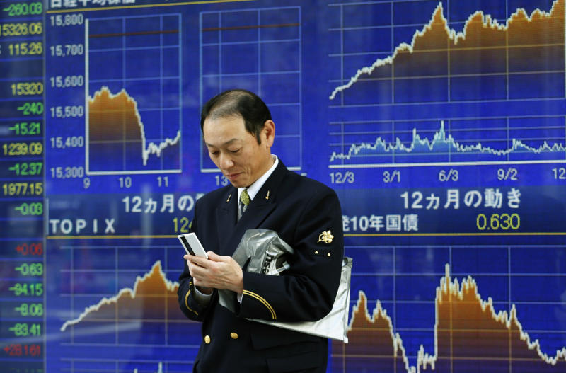 A man uses a mobile phone in front of an electronic stock indicator in Tokyo, Wednesday, Dec. 4, 2013. Most Asian stock markets fell Wednesday, led by losses in Japan, as investors continued to worry the U.S. Federal Reserve will soon start reducing its monetary stimulus. Japan's Nikkei 225 fell 2 percent to 15,407.94, pulling back from Tuesday's rise and levels that were the index's highest in about six months. (AP Photo/Shizuo Kambayashi)
