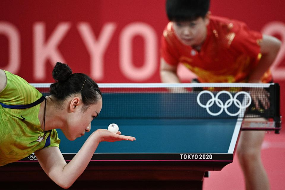 <p>Japan's Mima Ito (L) serves to China's Sun Yingsha during their women's singles semifinals table tennis match at the Tokyo Metropolitan Gymnasium during the Tokyo 2020 Olympic Games in Tokyo on July 29, 2021. (Photo by Anne-Christine POUJOULAT / AFP)</p>