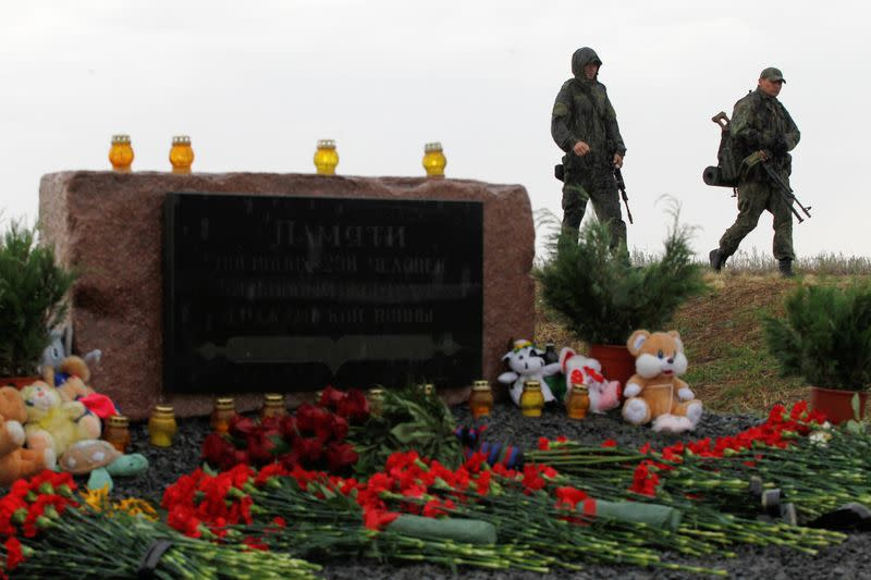 Members of the self-proclaimed Donetsk People's Republic forces walk past a memorial to victims of Malaysia Airlines Flight MH17 plane crash on the anniversary of the incident, outside the village of Hrabove in eastern Ukraine