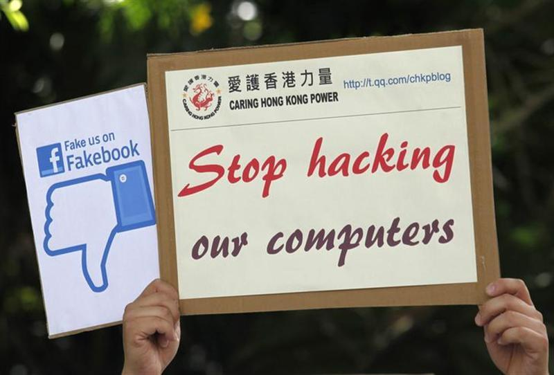 """A demonstrator from the pro-China """"Caring Hong Kong Power"""" group protests over claims from former U.S. spy agency contractor Edward Snowden that the National Security Agency (NSA) hacked computers in the Chinese territory, outside the U.S. Consulate in Hong Kong July 9, 2013."""