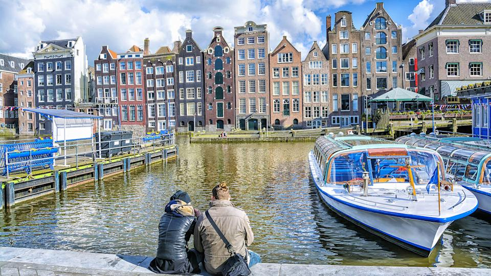 How Much to Tip When Traveling to These 25 Countries, Netherlands., Young love couple sitting on the waterfront against the canal in