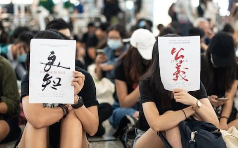 <span>Protesters hold papers of conscience, left, and justice</span> <span>Credit: PHILIP FONG/AFP </span>