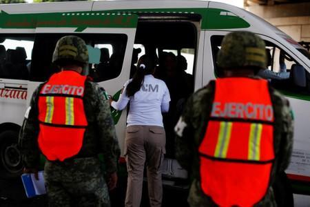Military police officers observe an immigration agent during a search at a checkpoint on a road in Tapachula