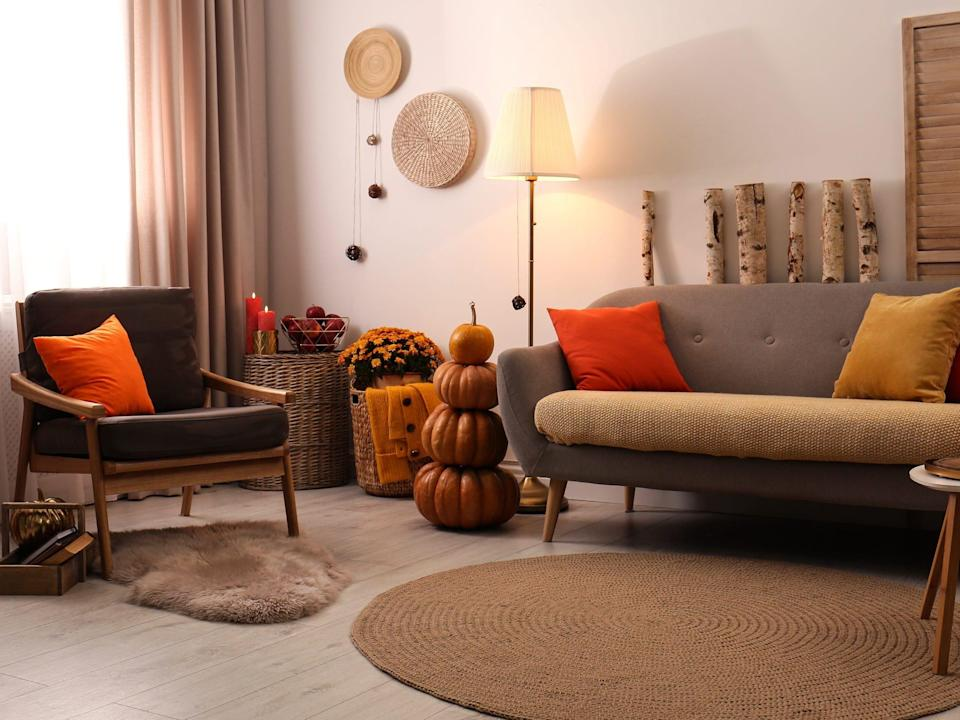 Neutral-toned living room with seasonal decor like candles, pumpkins, and orange pillows.