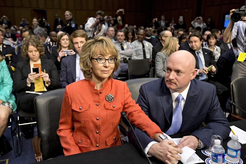 Former Arizona Rep. Gabrielle Giffords, who was seriously injured in the mass shooting that killed six people in Tucson, Ariz. two years ago, sits with her husband, Mark Kelly, right, a retired astronaut, on Capitol Hill in Washington, Wednesday, Jan. 30, 2013, prior to speaking before the Senate Judiciary Committee hearing on what lawmakers should do to curb gun violence in the wake of last month's shooting rampage at that killed 20 schoolchildren in Newtown, Ct. (AP Photo/J. Scott Applewhite)