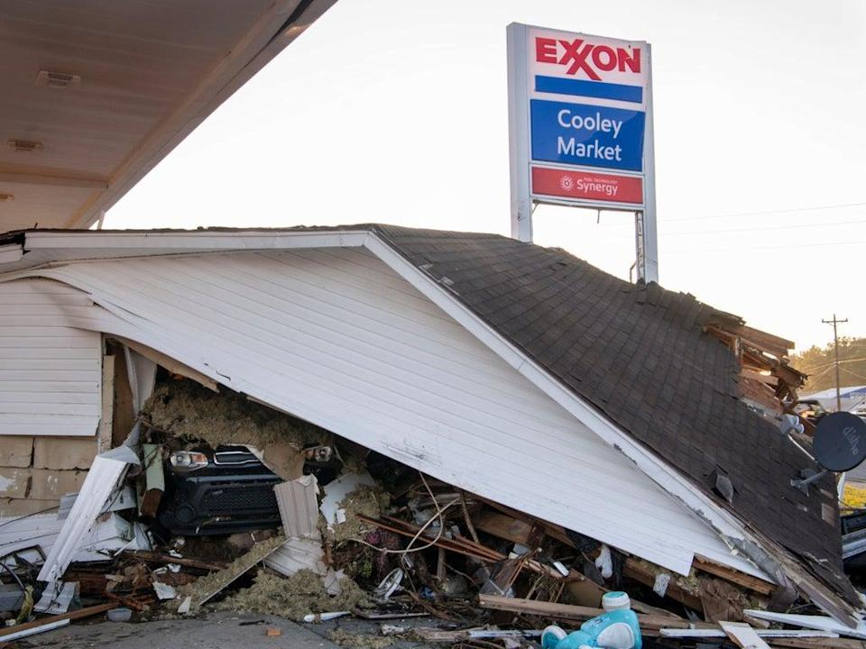 A car peeks out from under a house that was destroyed by floodwaters at the Cooley Market in Waverly, Tennessee (AP)