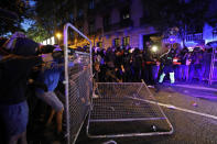 Protestors bring down a fence outside the Spanish Government Office in Barcelona, Spain, Tuesday, Oct. 15, 2019. Spain's Supreme Court on Monday convicted 12 former Catalan politicians and activists for their roles in a secession bid in 2017, a ruling that immediately inflamed independence supporters in the wealthy northeastern region. (AP Photo/Emilio Morenatti)