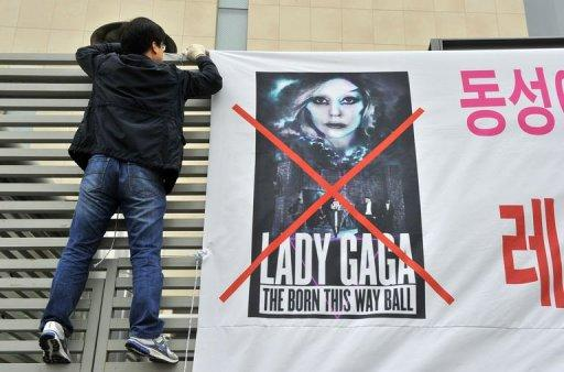 """A member of South Korea's Alliance for Sound Culture In Sexuality puts up a street banner against Lady Gaga's Seoul concert in downtown Seoul on April 23. Accused of contaminating youngsters with """"satanic"""" dance moves and """"intolerable"""" outfits, the cult of Lady Gaga is on a collision course with Asia's moral guardians ahead of her mammoth world tour"""