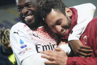 """AC Milan's Fikayo Tomori, left, embraces teammate Hakan Calhanoglu as his jersey sports a badge reading """"Keep racism out"""", part of the new anti-racism campaign launched last Sunday by the Italian soccer League, during a Serie A match between Fiorentina and AC Milan at the Artemio Franchi stadium in Florence, Italy, Sunday, March 21, 2021. Serie A's efforts to combat racism inside its stadiums was in shambles little more than a year ago when league CEO Luigi De Siervo decided to take matters into his own hands. (Spada/LaPresse via AP)"""