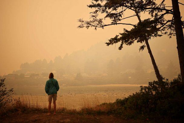 PHOTO: A woman looks at a town by the Pacific Ocean coast as smoke from wildfires covers an area near Yachats, Oregon, U.S., September 8, 2020. (Carlos Barria/Reuters)