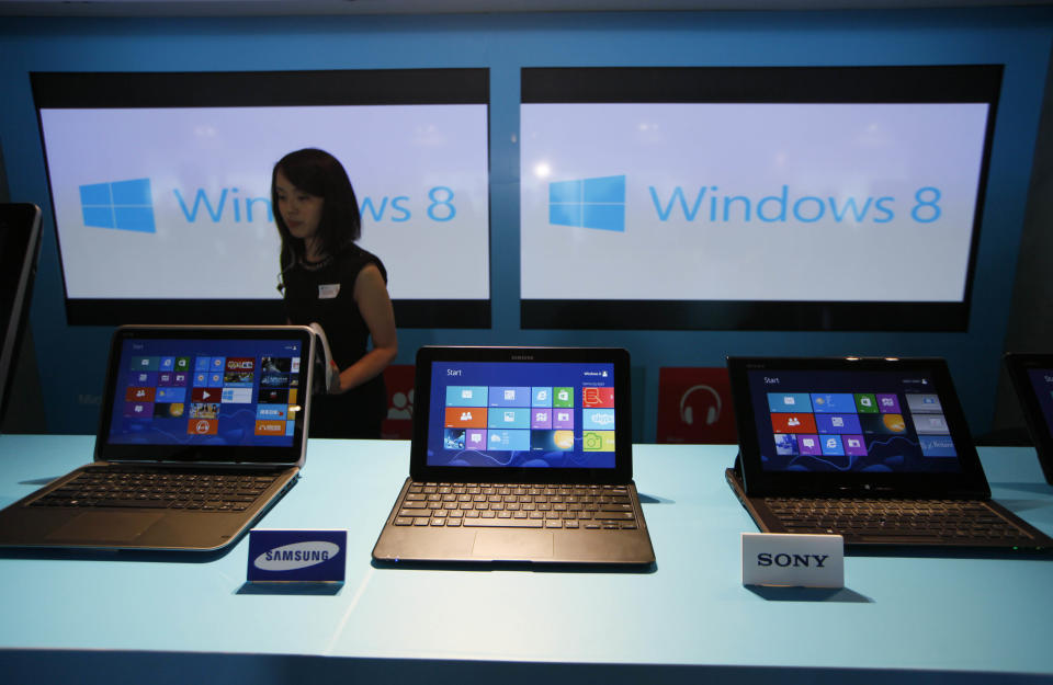 <p> FILE - In this Friday, Oct. 26, 2012, file photo, a woman walks past laptop computers running Microsoft Windows 8 operating system during its launching ceremony in Hong Kong. Research firm IDC says PC global shipments of PCs fell 14 percent in the first three months this year. The appeal of tablets and smartphones is pulling money away from PC sales, but it also blames Microsoft's latest version of Windows, which forces users to learn new ways to control their machines. (AP Photo/Kin Cheung, File)</p>
