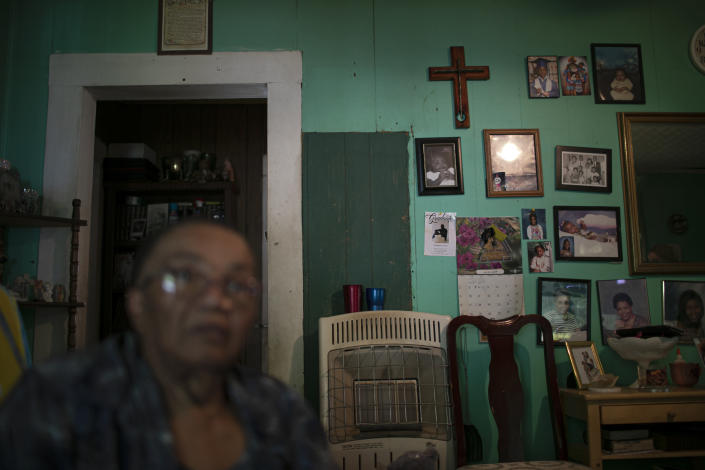 """Lou Alice Bolden with a crucifix and framed photographs in her home in Greenwood, Miss., Saturday, June 8, 2019. Known as """"Miss Lou,"""" Bolden has three grandsons who say they were sexually abused at a local Catholic grade school. (AP Photo/Wong Maye-E)"""