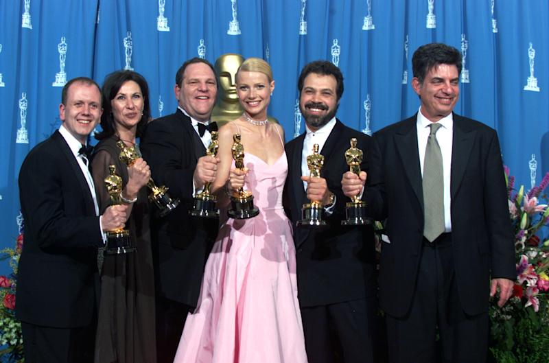 "LOS ANGELES, CALIFORNIA - MARCH 21 : ""Shakespeare in Love' Best Actress winner Gwyneth Paltrow (center) is joined by Harvey Weinstein (center lett) David Parfitt (left), Donna Gigliotti,Edward Zwick and Marc Norman (right) backstage as they celebrated their win of Best Picture at the 1999 Academy Awards in Hollywood, California, March 21, 1999.(Photo by Bob Riha, Jr./Getty Images)"