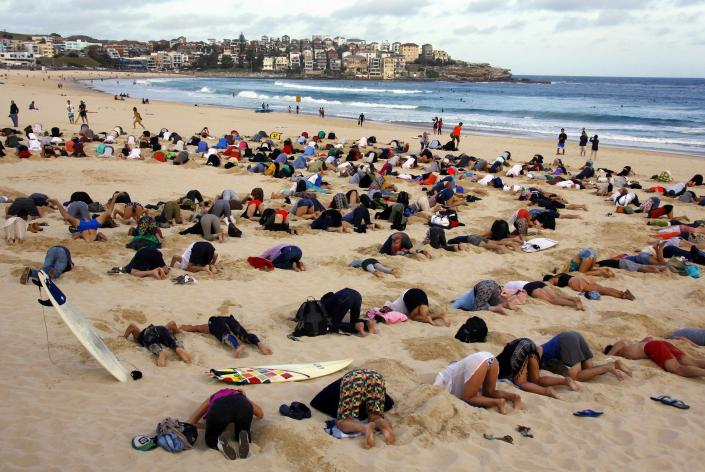 """A group of around 400 demonstrators participate in a protest by burying their heads in the sand at Sydney's Bondi Beach November 13, 2014. Hundreds of protesters participated in the event, held ahead of Saturday's G20 Leader's Summit in Brisbane, which was being promoted as a message to Australian Prime Minister Tony Abbott�s government that, """"You have your head in the sand on climate change"""". REUTERS/David Gray (AUSTRALIA - Tags: POLITICS CIVIL UNREST SOCIETY ENVIRONMENT)"""