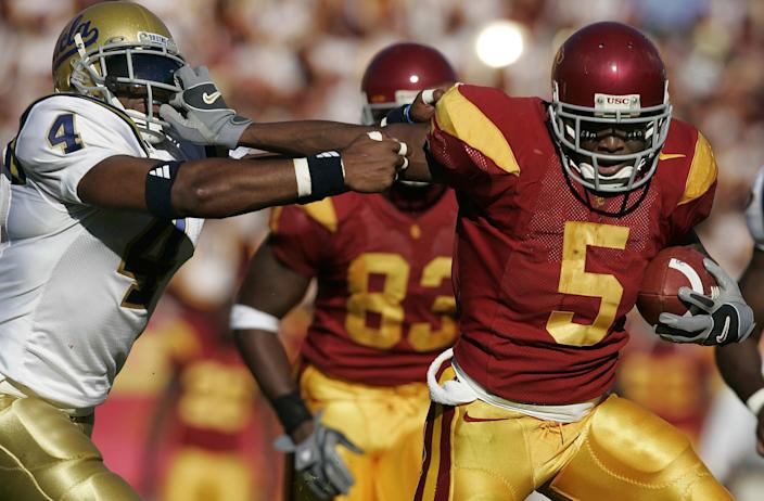 USC's Reggie Bush stiff arms UCLA's Jarrad Page during a game in 2005.