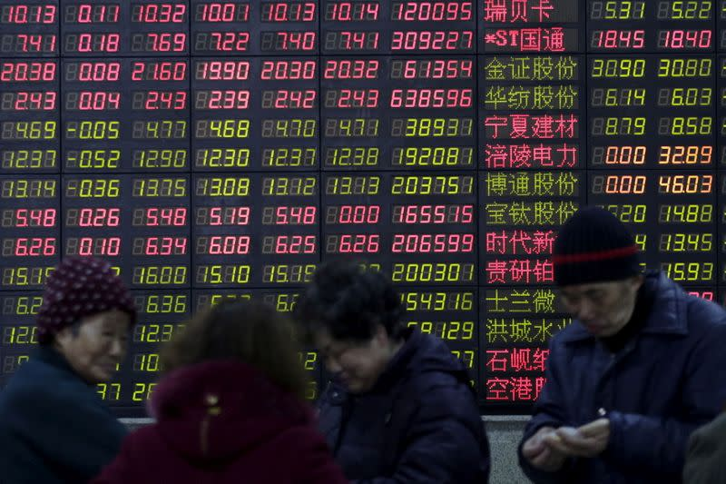 FILE PHOTO: FILE PHOTO: Investors stand in front of an electronic board showing stock information on the first trading day after the week-long Lunar New Year holiday at a brokerage house in Shanghai