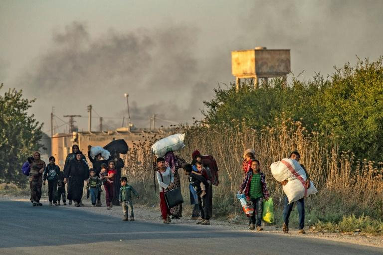 Civlians flee from the Turkish bombardment on the northeast Syrian town of Ras al-Ain (AFP Photo/Delil SOULEIMAN)
