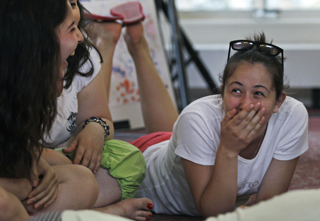 "Amina Sabanova, of Russia, right, laughs with Alla Nogaeva, of Russia, while attending the ""Common Bond"" summer camp in Newbury, Mass., Wednesday, July 18, 2012.  Teens from across the world who lost loved one due to terrorism gathered for the 10 day camp to share their feelings, insights and a chance to be the worldís next generation of international peacemakers. Both girls lost family members in a school hostage crisis in Beslan, Russia during 1994 where more than 350 were killed. (AP Photo/Charles Krupa)"