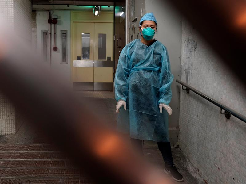 A personnel wearing protective suit waits near an entrance at the Cheung Hong Estate, a public housing estate during evacuation of residents in Hong Kong, Tuesday, Feb. 11, 2020. The Centre for Health Protection of the Department of Health evacuated some residents from the public housing estate after two cases of novel coronavirus infection to stop the potential risk of further spread of the virus. (AP Photo/Kin Cheung)