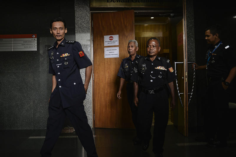 Witnesses ASP Azizie Mohd (left) leaves the courtroom after appearing before the Wang Kelian Royal Commission of Inquiry (RCI) in Putrajaya April 17, 2019. — Picture by Miera Zulyana