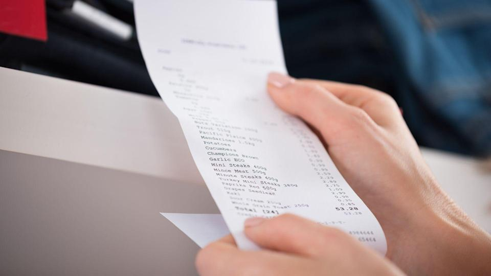Cropped image of woman holding receipt in store