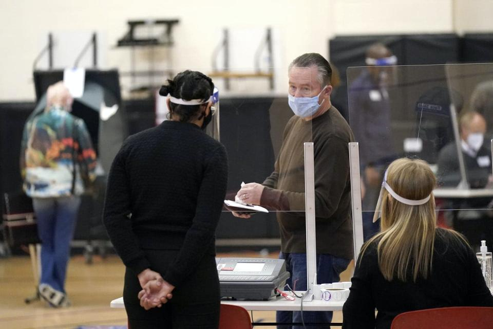 A voter and a poll workers, both wearing masks, have a conversation at a polling station.
