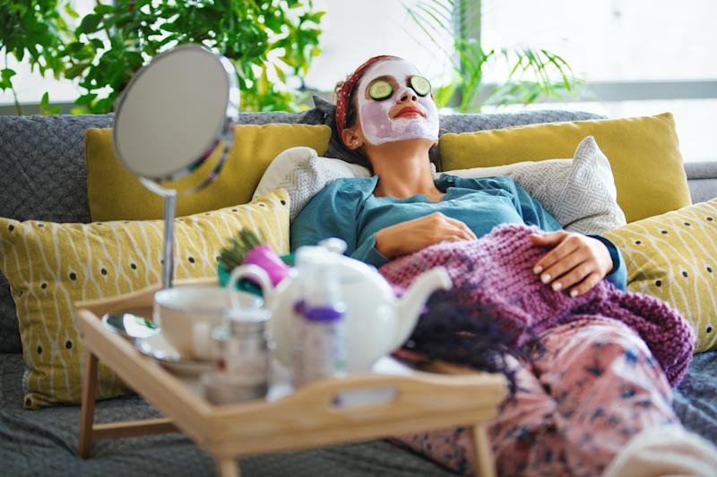 Young woman with a mask and rolls of cucumber on her face is enjoying a morning weekend.