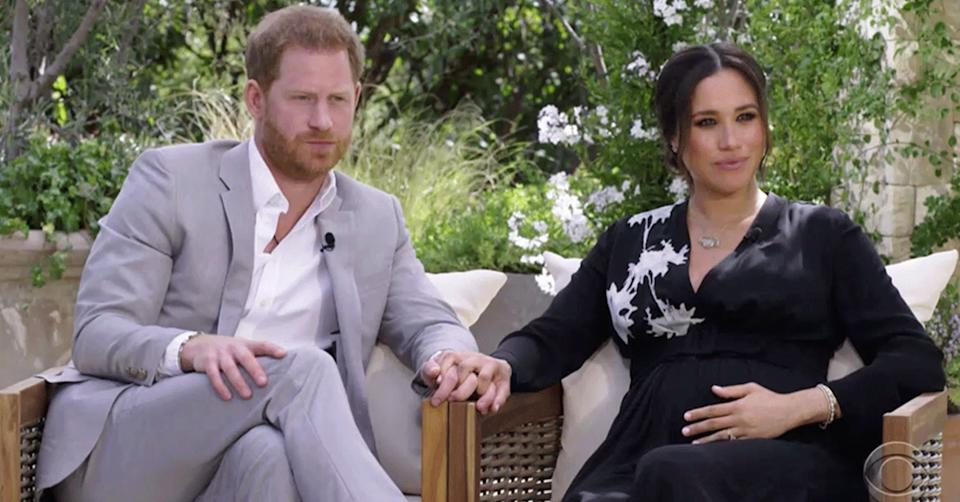 Prince Harry and Meghan Markle hold hands during an interview with Oprah Winfrey on CBS. Photo: CBS.