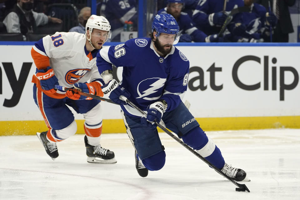 Tampa Bay Lightning right wing Nikita Kucherov (86) beats New York Islanders left wing Anthony Beauvillier (18) to a loose puck during the first period in Game 1 of an NHL hockey Stanley Cup semifinal playoff series Sunday, June 13, 2021, in Tampa, Fla. (AP Photo/Chris O'Meara)
