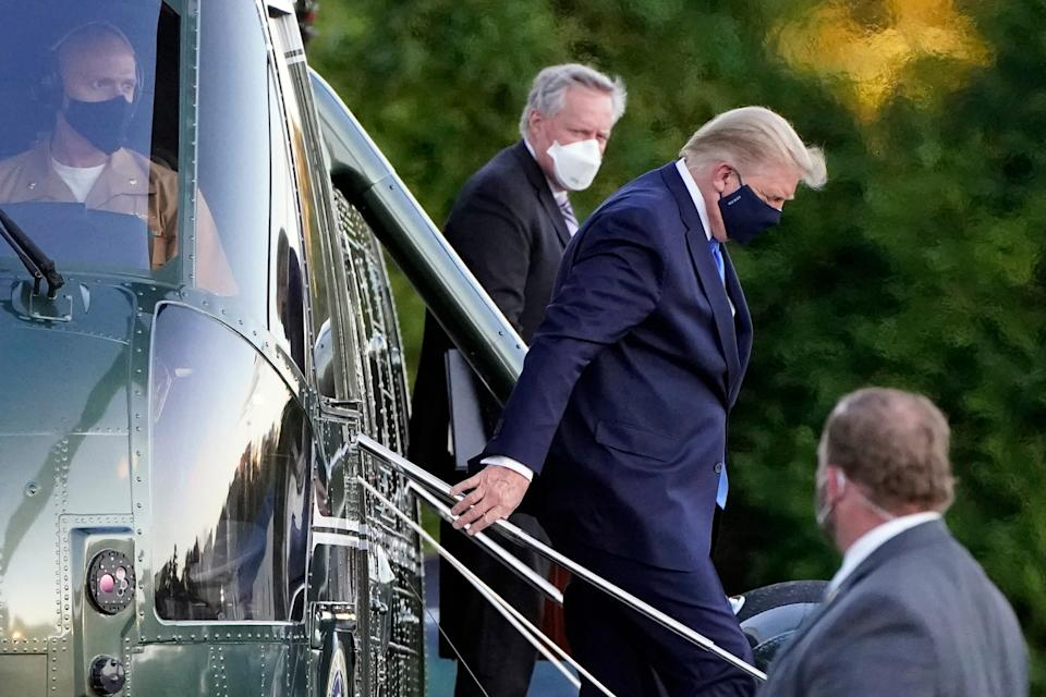 President Donald Trump arrives at Walter Reed National Military Medical Center, in Bethesda, Md., Friday, Oct. 2, 2020, on Marine One helicopter after he tested positive for COVID-19. White House chief of staff Mark Meadows is at second from left.