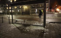In this grab taken from video on Monday, Jan, 25, 2021, a person stands at a bus stop where the glass has been shattered after rioting, in Haarlem, Netherlands. Groups of youths have confronted police in several Dutch cities defying the country's coronavirus curfew and throwing fireworks. Police in the port city of Rotterdam used a water cannon and tear gas in an attempt to disperse a crowd of rioters Monday night. (Mizzle Media via AP)