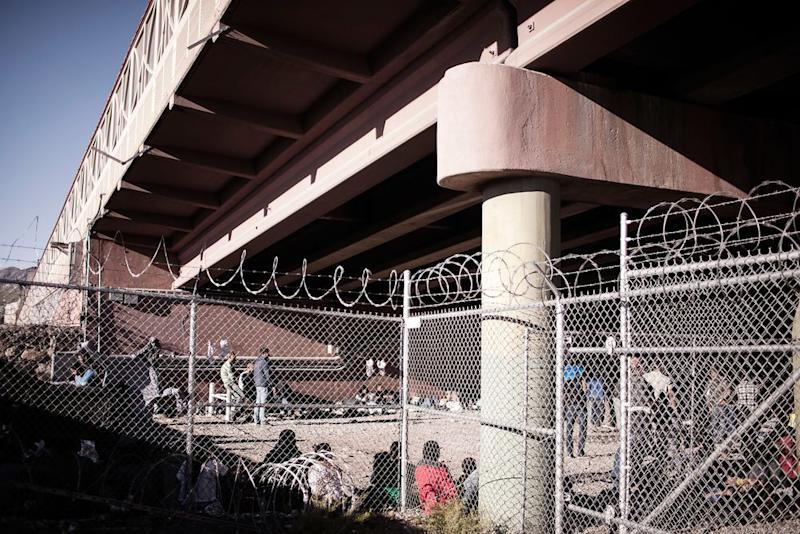 Detained migrants held within temporary fencing underneath the Paso Del Norte Bridge in El Paso, Texas on March 28, 2019. Due to the large volume of apprehensions within the area, the agency has set up a temporary facility within the last month. | Jared Moossy for TIME
