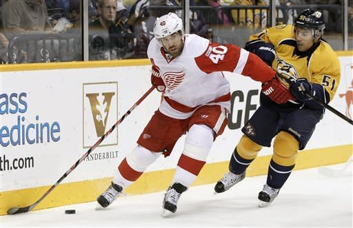 Detroit Red Wings center Henrik Zetterberg (40), of Sweden, protects the puck from Nashville Predators defenseman Francis Bouillon (51) in the first period of an NHL hockey game on Monday, Dec. 26, 2011, in Nashville, Tenn. (AP Photo/Mark Humphrey)