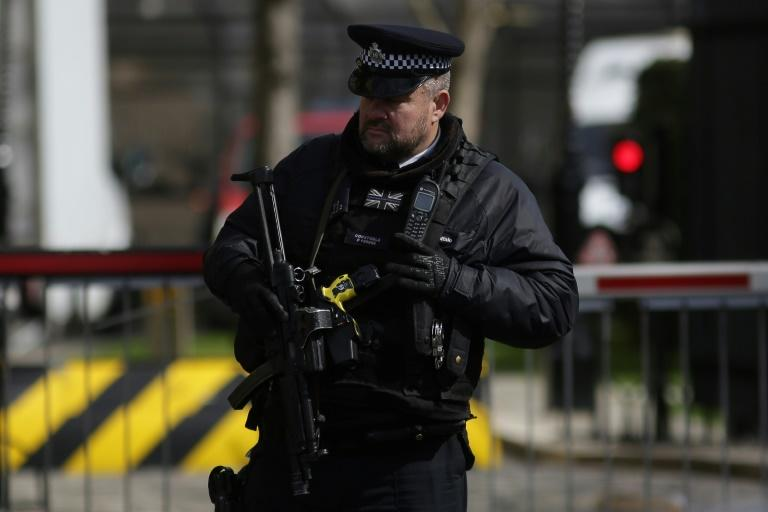 An armed police officer stands at an entrance to the Houses of Parliament in central London on March 26, 2017