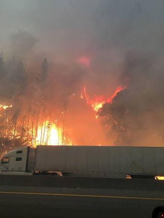 Flames engulf trees along interstate 5 in the Shasta-Trinity National Forest as a tractor trailer drives by north of Redding