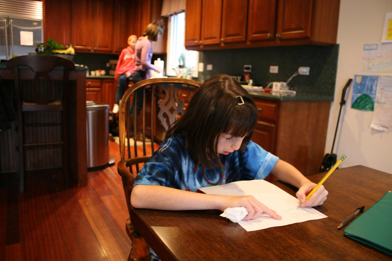 In this Feb. 22, 2012 photo, Clara Beatty, 9, works on math homework in her Winnetka, Ill., home. Clara, who was born with facial deformities caused by a genetic mutation called Treacher Collins syndrome, says math and reading are her favorite subjects. She hopes to be a doctor some day. (AP Photo/Martha Irvine)