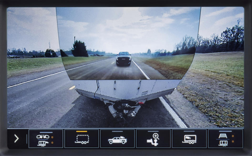 This image provided by General Motors, shows the display of a 2020 GMC Sierra HD feature called Transparent Trailer, one of the few pickup trucks that provides an image of the road behind a trailer. This optional feature uses augmented reality to project an image of the road on the front of a trailer, giving the illusion of a transparent trailer. (General Motors via AP)