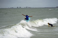 Luis Ernesto catches a small wave while surfing along Pass-a-Grille Beach, Wednesday, July 7, 2021 in St. Pete Beach, Fla., the morning after Tropical Storm Elsa moved over the Tampa Bay Area. (Martha Asencio-Rhine/Tampa Bay Times via AP)